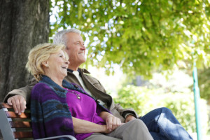Senior couple relaxing at outdoors. Portrait of happy elderly woman and friendly old man sitting at park and relaxing.